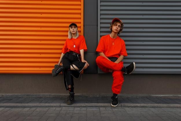 Schöne modische junge stilvolle paare in mode orange kleidung mit kappen sitzen in der nähe der metall grau und orange wand