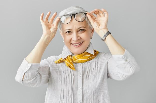 Schöne modische kaukasische rentnerin mit weitsicht, die ihre brille abnimmt, um sich auf nähere objekte zu konzentrieren, breit lächelnd. konzept für ältere menschen, alterung und sehprobleme