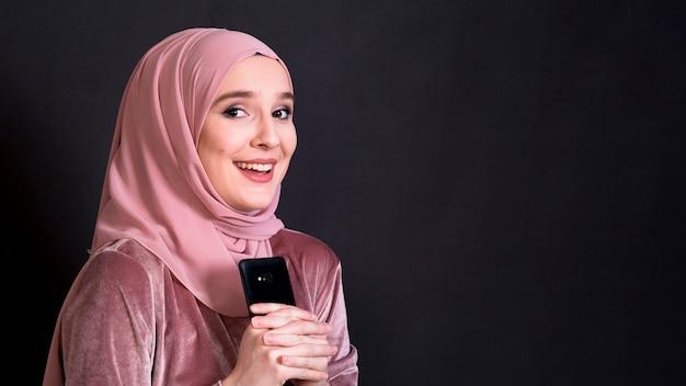 Schöne moslemische frau, welche die kamera hält handy auf schwarzem hintergrund betrachtet