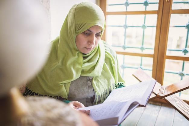 Schöne moslemische junge frau innerhalb der moschee, die koran des heiligen buches liest
