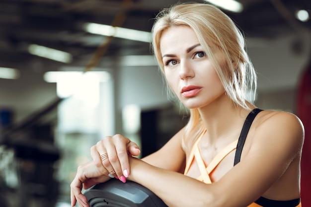 Schöne müde blonde frau auf dem laufband im fitnessstudio nach dem training.