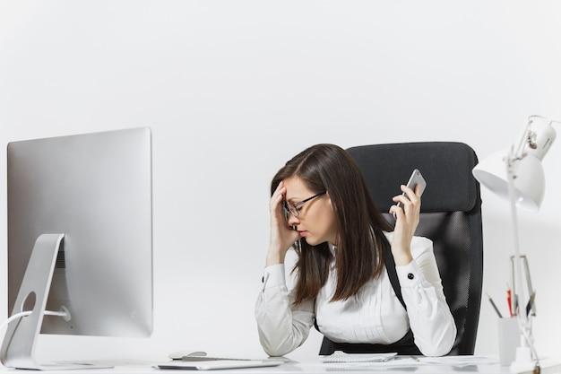 Schöne müde und gestresste geschäftsfrau im anzug, die am schreibtisch sitzt, am modernen computer mit dokumenten im hellen büro arbeitet, mit dem handy spricht, probleme löst