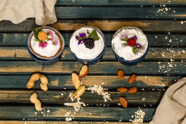 Schöne muffins mit beeren auf hölzernem hintergrundnusshonig