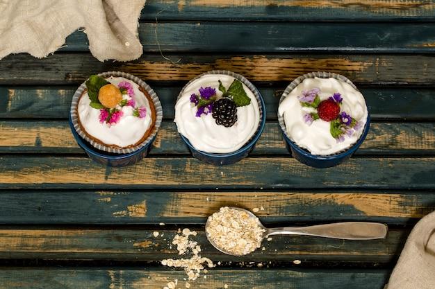 Schöne muffins mit beeren auf hölzernen tischnüssen honig