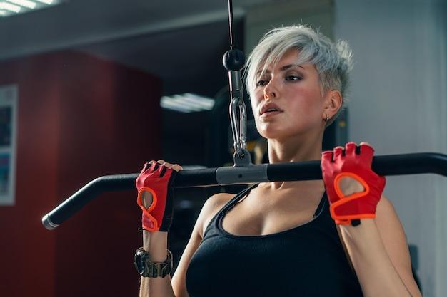 Schöne muskulöse fit frau, die aufbauende muskeln ausübt