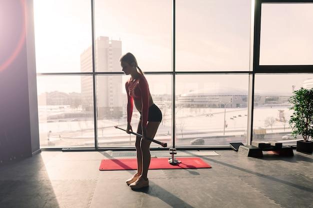 Schöne muskulöse frau, die übung mit gymnastikstock in einer turnhalle tut. schwedische wand im hintergrund