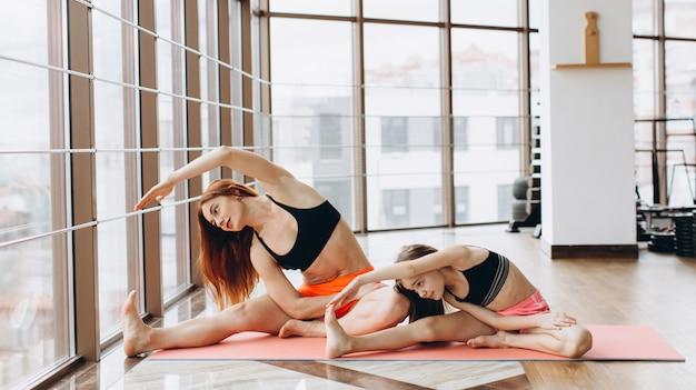 Schöne muskulöse frau und ihre charmante kleine tochter lächeln, während sie zusammen yoga im fitnessstudio machen