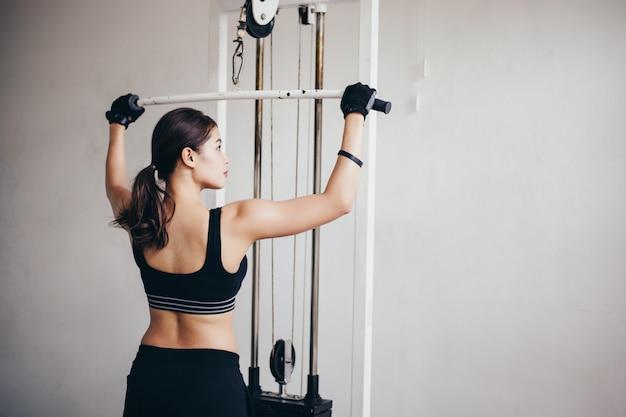 Schöne muskulöse sitzfrau, die errichtende muskeln und frau, die übungen tut