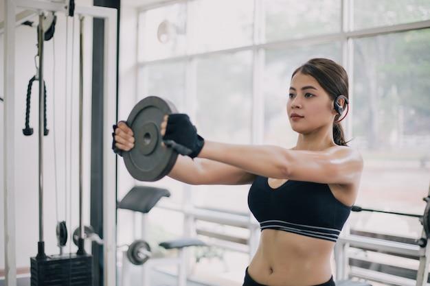 Schöne muskulöse sitzfrau, die gebäudemuskeln und die eignungsfrau tut übungen in der turnhalle ausübt.