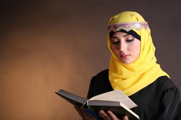 Schöne muslimische arabische frau, die buch liest