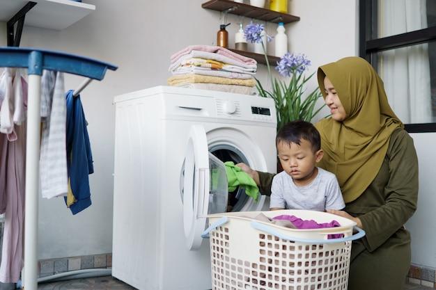 Schöne muslimische asiatische frau, die wäsche mit ihrem sohn zusammen macht
