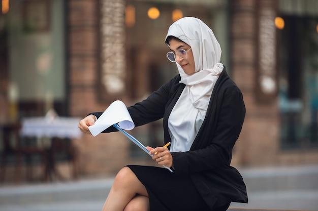 Schöne muslimische erfolgreiche geschäftsfrau liest dokument auf der straße