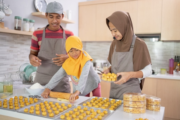 Schöne muslimische familie, die zu hause zusammen nastar-ananaskuchen der indonesischen tradition macht