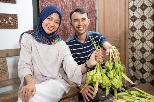 Schöne muslimische familie und freunde, die zu hause ketupat-reiskuchen mit palmblättern für die eid fitr mubarak-tradition herstellen