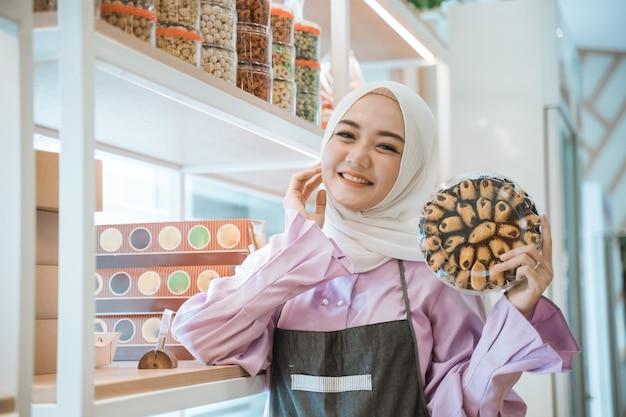 Schöne muslimische frau des ladenbesitzers, die einen kuchen für eid mubarak in ihrem laden hält