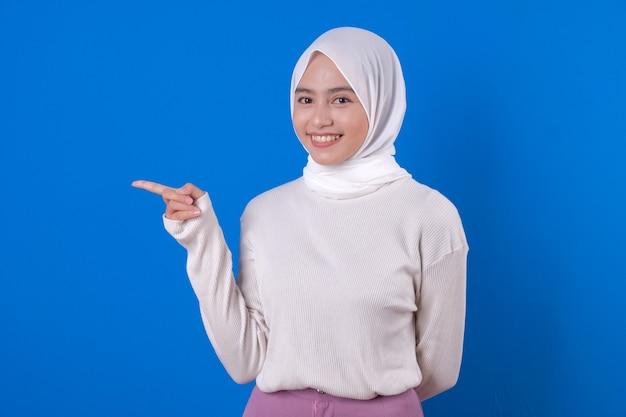 Schöne muslimische frau, die ihren zeigefinger zeigt