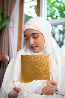 Schöne muslimische frau, die koran hält