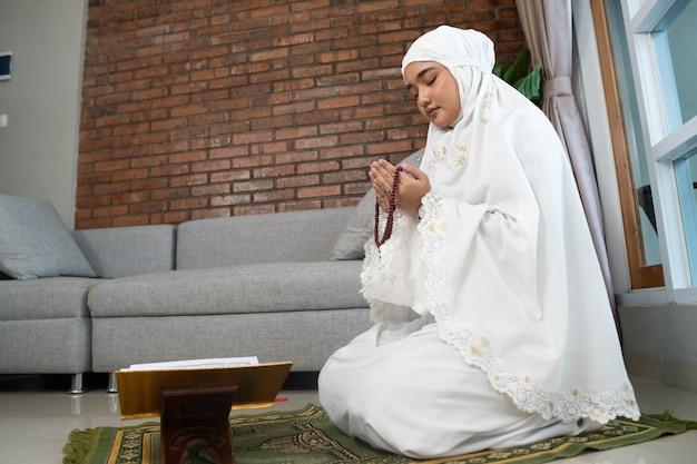 Schöne muslimische frau, die koran liest