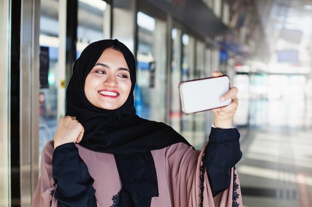 Schöne muslimische frau, die selfie macht