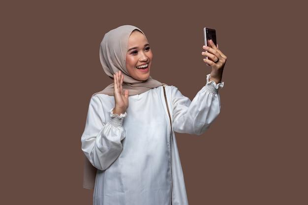 Schöne muslimische frau im hijab, die einen videoanruf mit einem handy macht, während sie grüßt und lächelt