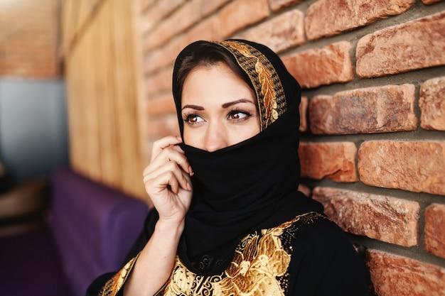 Schöne muslimische frau in traditioneller kleidung, die ihr gesicht mit schal bedeckt, während sie in der cafeteria sitzt.