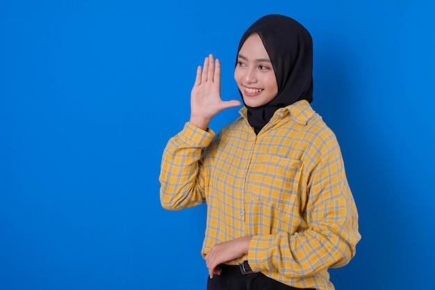 Schöne muslimische frau mit der rechten hand flüsterte ausdruck