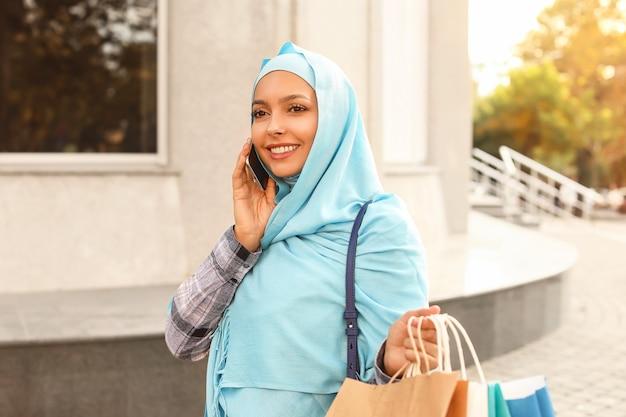 Schöne muslimische frau mit einkaufstaschen, die durch telefon im freien sprechen