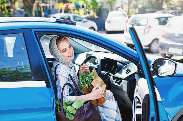 Schöne muslimische frau mit einkaufstüten, die in einem blauen auto sitzt und fahren will