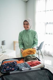Schöne muslimische frauen, die kleidung vorbereiten, um in einen koffer gelegt zu werden