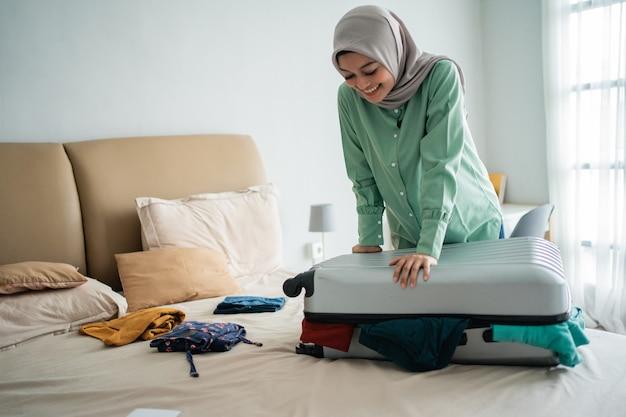 Schöne muslimische frauen, die versuchen, ihren vollen koffer zu schließen