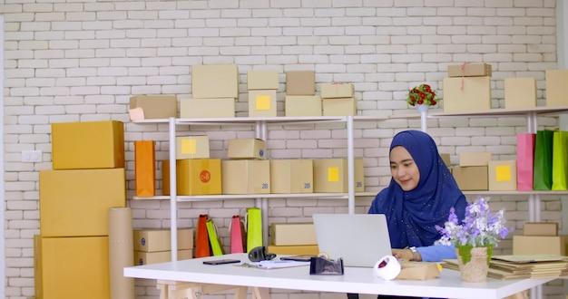 Schöne muslimische händlerin, die online-marketing im büro macht.