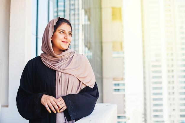 Schöne muslimische indische frau im hijab, die über dubai-stadthintergrund lächelt