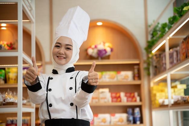 Schöne muslimische köchin mit hijab, die stolz in ihrem geschäft steht und daumen hoch zeigt