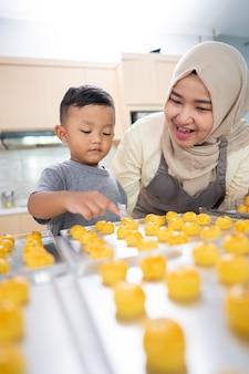 Schöne muslimische mutter, die mit ihrem sohn zu hause zusammen kuchen für eid mubarak macht