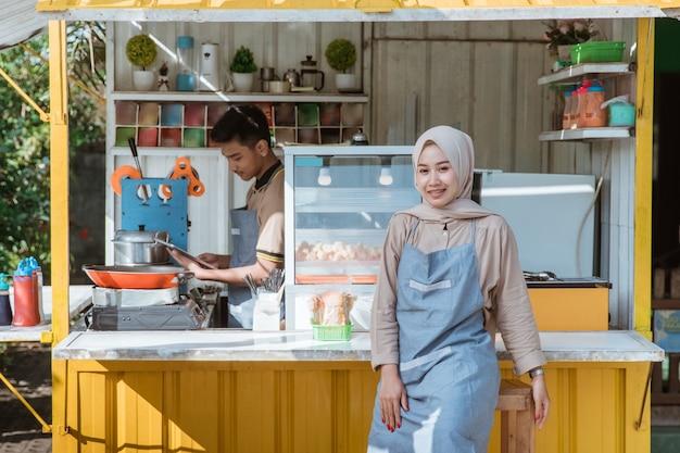 Schöne muslimische unternehmerin an ihrem kleinen essensstand