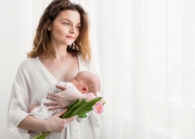 Schöne mutter, die beim tragen ihres babys, das nahe weißem vorhang steht, weg schaut