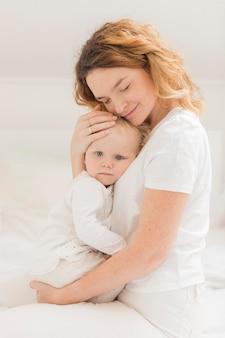 Schöne mutter, die ihr baby hält