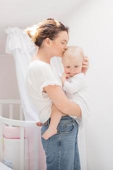 Schöne mutter, die ihr baby küsst