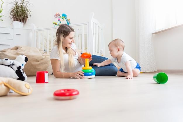 Schöne mutter, die mit ihrem baby auf dem boden spielt
