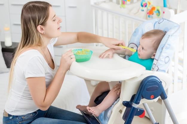 Schöne mutter füttert ihr baby im hochstuhl mit brei