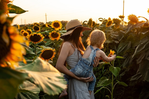 Schöne mutter hält einen kleinen sohn auf einem sonnenblumenfeld. zärtlichkeit, lächeln, glück.
