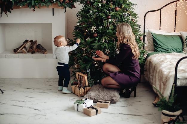 Schöne mutter hilft ihrem kleinen sohn, einen weihnachtsbaum zu schmücken
