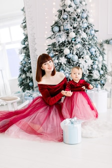 Schöne mutter im roten kleid posiert mit ihrem niedlichen kleinen mädchen im gemütlichen lichtdekorierten studio