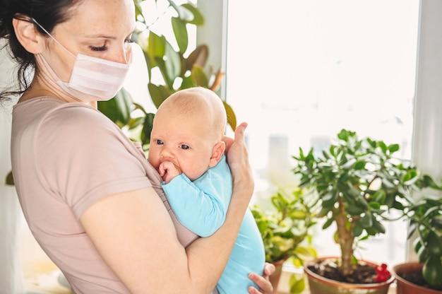 Schöne mutter in der schützenden gesichtsmaske, die ihren kleinen niedlichen neugeborenen sohn hält, der ihn vor viren und infektionen schützt.
