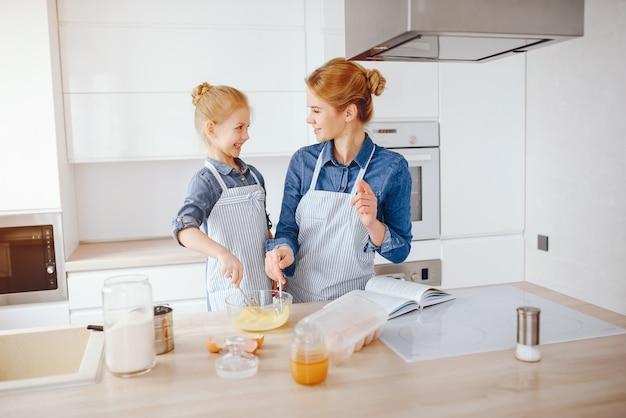 Schöne mutter in einem blauen hemd und schürze bereitet abendessen zu hause in der küche vor