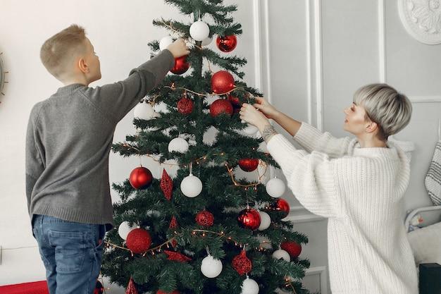 Schöne mutter in einem weißen pullover. familie in einer weihnachtsdekoration. kleiner junge in einem raum
