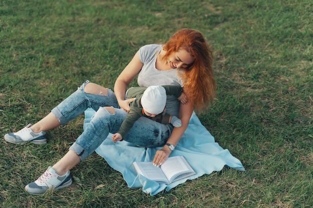 Schöne mutter liest ein buch mit ihrem süßen jungen