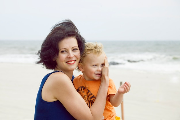 Schöne mutter mit einem niedlichen sohn auf einem spaziergang. familienfoto am strand.