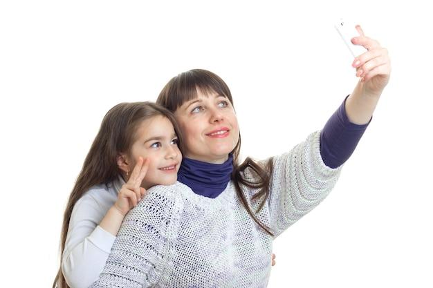 Schöne mutter mit ihrer tochter macht selfie isoliert auf weißem hintergrund