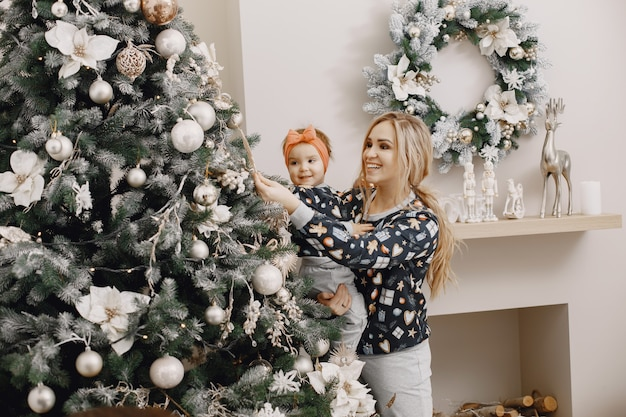 Schöne mutter mit kind. familie in weihnachtsatmosphäre. leute, die weihnachtsbaum tragen.